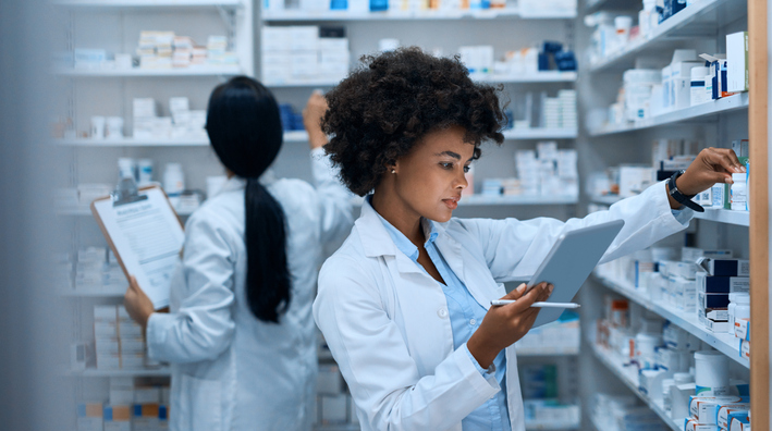 Female Pharmacist Checking Inventory on Tablet