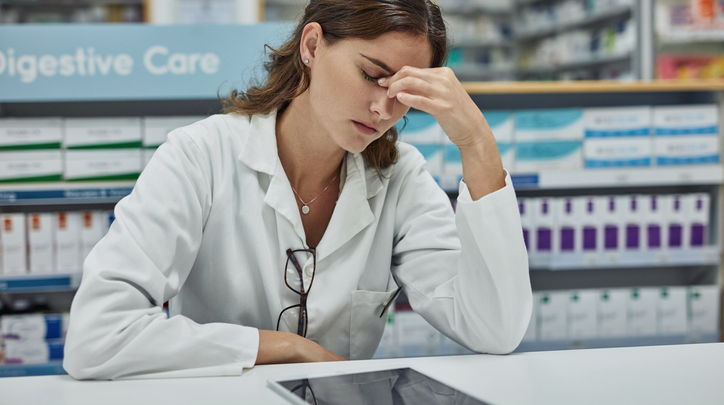 Frustrated Pharmacist Sitting with Tablet