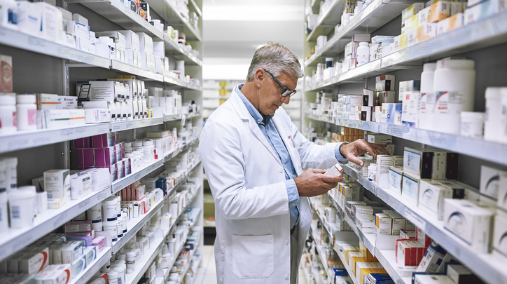 Older Male Pharmacist Stocking Shelves
