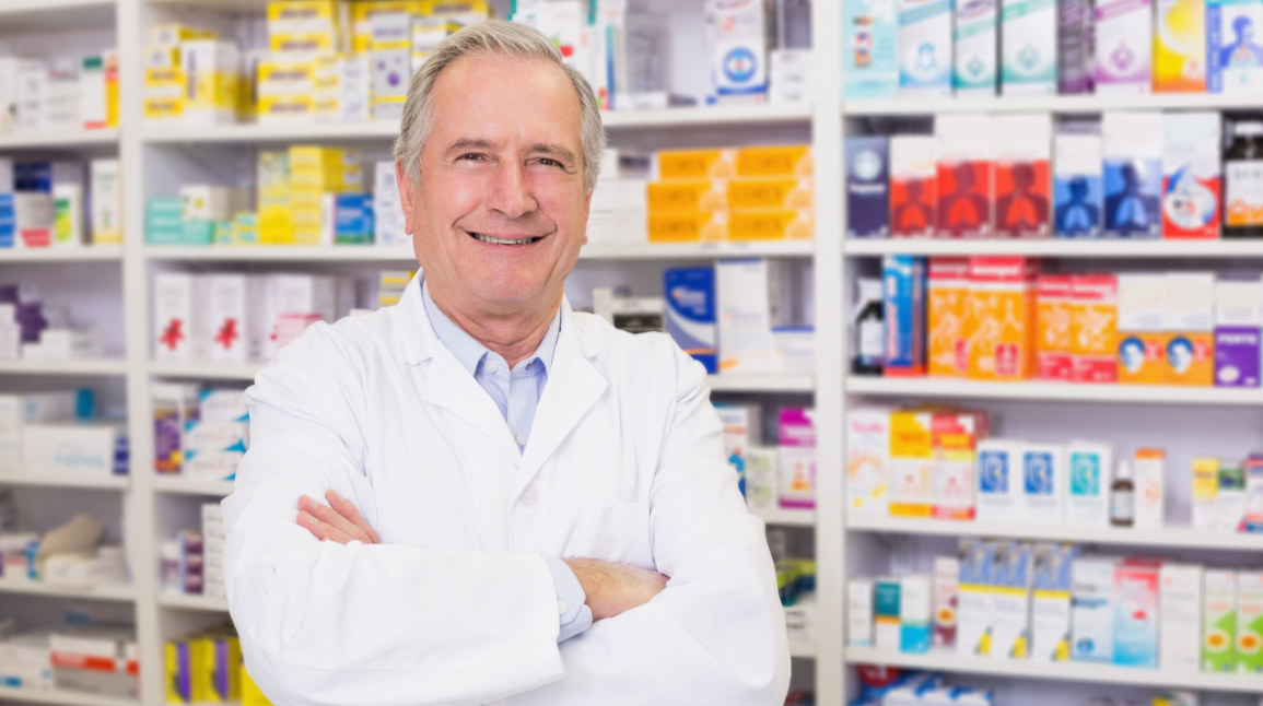Older Male Pharmacist in Front of Medications