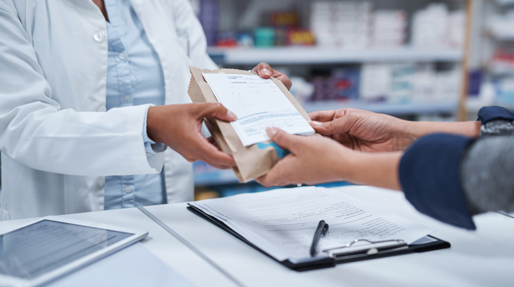 Pharmacist Handing Patient Medication Bag