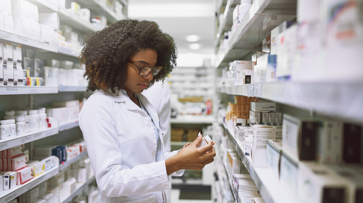 Young Female Pharmacist Stocking Shelves